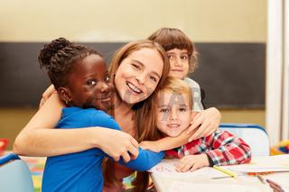 Glückliche Kinder umarmen ihre Erzieherin