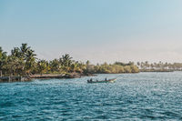 two persons in small motorboat on ocean with tropical palm tree island landscape