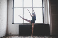 Plasticity slim woman dancing near window. Professional dancer enjoy dance. Lady Dancer Training Modern Ballet In Class. Contemporary dance performer. Daylight, silhouette beautiful body. Dance theme