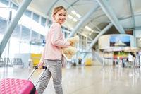 Alleinreisendes Mädchen mit Rollkoffer im Flughafen