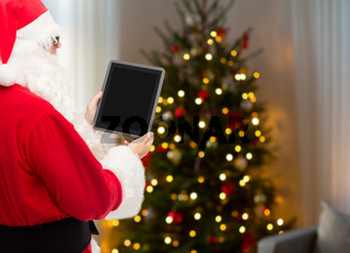 santa claus with tablet pc over christmas tree