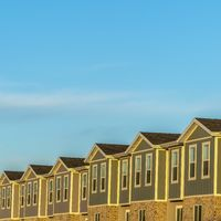 Square Townhomes against snow topped mountain and bright blue sky on a sunny day