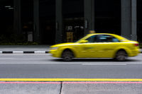 Yellow taxi of Singapore drives past in a motion blur on empty city road.