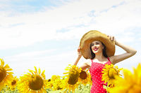 Pretty woman wearing the big hat in sunflower field