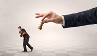 Small businessman running away from big hand with chessman concept