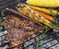 T bone steak cooking on fire with vegetables