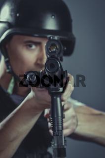 warrior paintball sport player wearing protective helmet aiming pistol ,black armor and machine gun