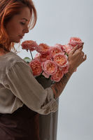 Delicate pink bouquet of roses in a vase holds in hands a pretty red-haired woman with a tattoo around a gray background with space for text. Mothers Day