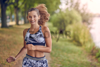 Fit healthy athletic woman jogging on a river bank