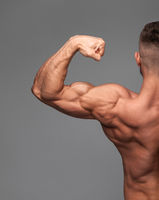 Handsome power athletic man bodybuilder demonstrates his biceps.