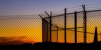Mesh wire fence and barbeb wire at sunset