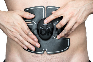 Male athlete wearing a electric ab muscle stimulator doing abs exercise