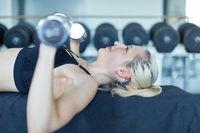 Frau trainiert mit Kurzhanteln die Brustmuskeln