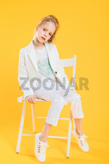 A teenage girl in white clothes is sitting on a chair on a yellow background.