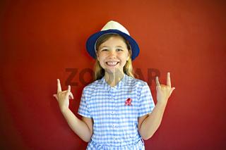 Pretty emothional children wear a hat on a red background