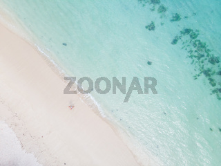 Aerial shot of woman enjoying the picture perfect white tropica beach on Mauritius island.