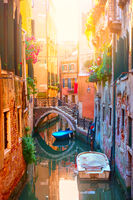Picturesque small canal with bridge and boats in Venice