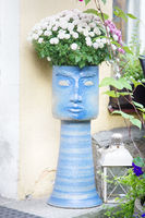 Street vase with flowers in the form of a female mask