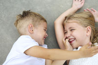 Portrait of adorable brother and sister smile and laugh together outdoors