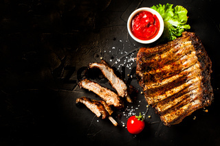 Grilled sliced barbecue pork ribs on the black background