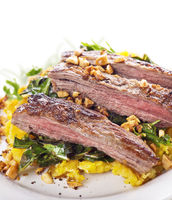 flank steak with mashed plantain , collard greens and ginger peanuts