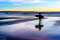 Couple with surfboards at sunset