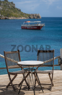 Wooden chairs and  table on a deck platform