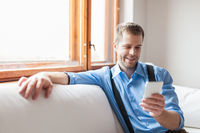 Handsome man sitting on sofa and texting from his smart phone