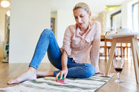 Hausfrau entfernt Rotweinflecken vom Teppich