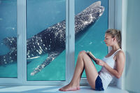 Young woman imaginating underwater sea life and dreaming while reading book