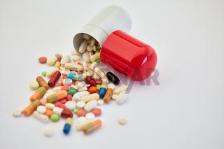 Haufen Medikamente purzelt aus großer Kapsel