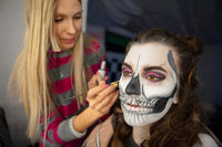 Makeup artist puts face painting of a beautiful woman