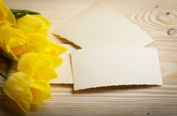 Yellow tulips and blank greeting card on natural wooden background with space for text