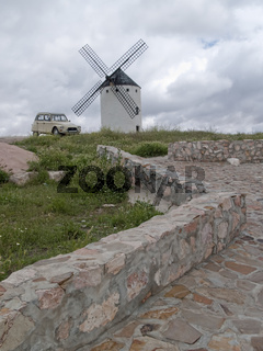 Don Quixote's windmill with old Citroen Dyane car in cloudy afternoon
