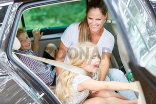 Mutter hilft Kind beim Anschnallen im Auto
