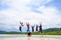 Happy family jumping together on the beach, Thailand