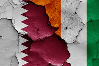 flags of Qatar and Ivory Coast painted on cracked wall