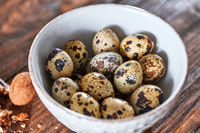 On the wooden table is a white ceramic bowl with organic quail eggs and a walnut. Healthy food. Top view