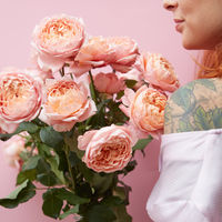 A young girl with a tattoo is holding a bouquet of elegant pink roses around her pink background.