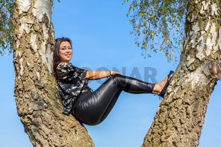 Woman sits in birch tree with blue sky