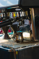 Close-up of espresso pouring from coffee machine inside small chromed bowl. Professional coffee brewing
