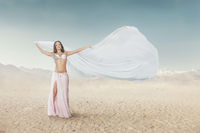Portrait of beautiful young woman dancing belly dance outdoor at sandy desert