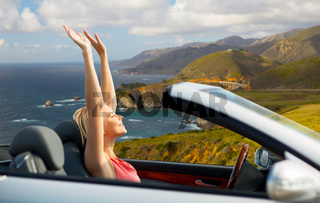 happy woman in convertible car on big sur coast