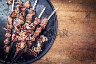 Traditional Russian shashlik on a barbecue skewer with roasted onion as top view on cutting board with copy space right