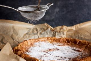 Kuchen wird mit Puderzucker dekoriert