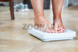 Woman Standing on Scale At Home Covering Weight Results With Toes