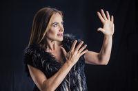 Woman in black mask performing in studio