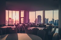 empty dinner table in room with view over modern skyline during sunset