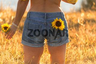 Girl wearing denim shorts holding sunflower in a sunny field