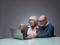 Senior couple looking at laptop